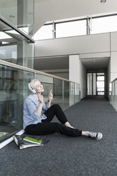 Woman sitting on office floor enjoying listening to music with headphones - UUF13371