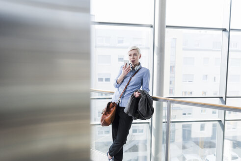 Woman in office building using cell phone - UUF13380