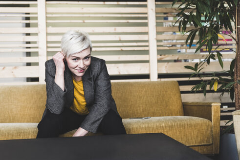 Portrait of smiling casual businesswoman sitting on couch in lounge - UUF13386