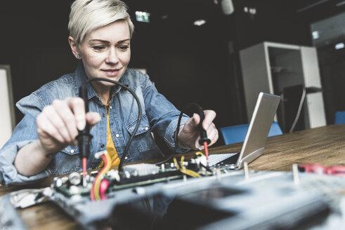 Woman working on computer equipment - UUF13392