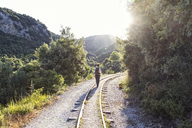 Greece, Pilion, Milies, back view of man walking along rails of Narrow Gauge Railway - MAMF00049