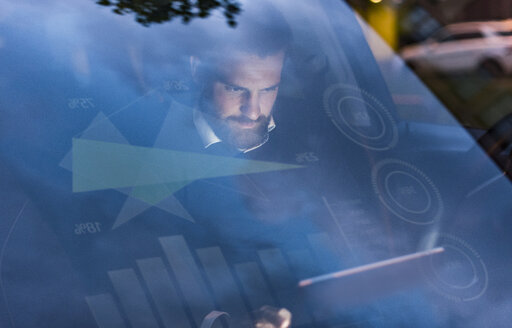 Businessman with tablet in car at night surrounded by data - UUF13401