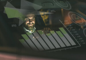 Smiling businessman with smartphone in car at night surrounded by data - UUF13404