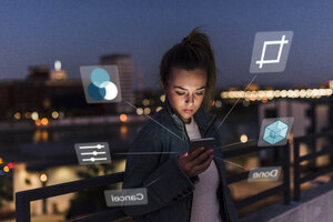 Young woman outdoors at night with data emerging from smartphone - UUF13410