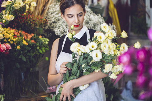 Female florist holding bunch of flowers in shop - CAVF39146