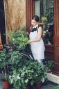 Female florist arranging leaves in basket outside shop - CAVF39164