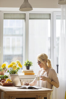 Woman with drink using laptop computer while sitting by window at home - CAVF39182