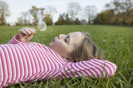 Side view of girl blowing dandelion while lying on grassy field in park - CAVF39329