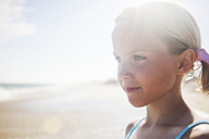 Close-up of cute girl looking away while standing at beach against sky - CAVF39344
