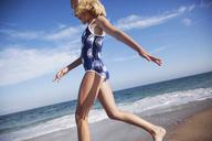 Low angle view of girl in bikini walking at beach - CAVF39347