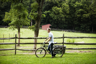 Man with bicycle walking by fence in farm - CAVF39398