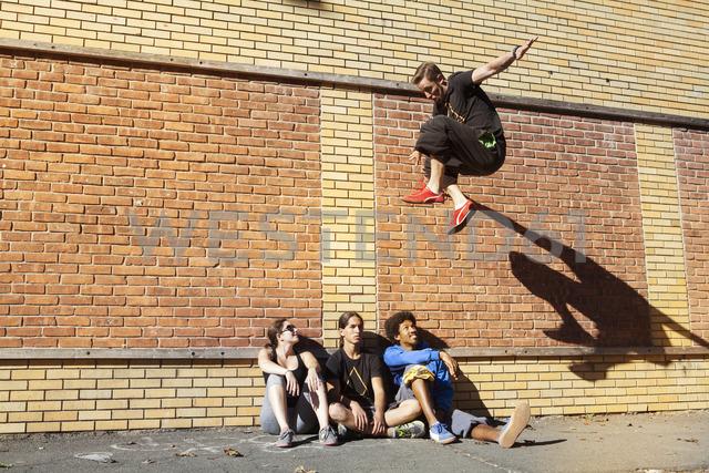 Friends looking at man doing stunt on footpath - CAVF39434 - Cavan Images/Westend61