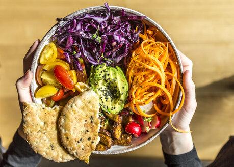 Girl holding veggie bowl with tomato, tofu, red cabbage, avocado, carrot, red redish, cress, black sesame and pita bread - SARF03660