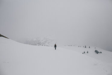 Austria, Kitzbuehel, woman walking in snow-covered landscape - GUSF00626