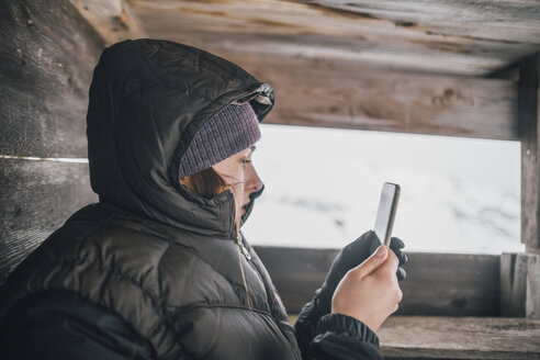 Austria, Kitzbuehel, young woman in raised hide looking at cell phone in winter - GUSF00632