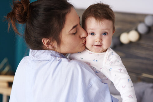 Mother carrying and kissing her baby at home - ABIF00306