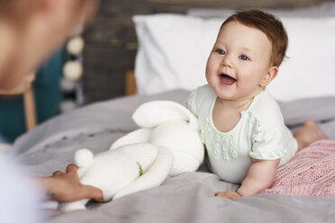 Happy baby with cuddly toy on bed at home looking at her mother - ABIF00318