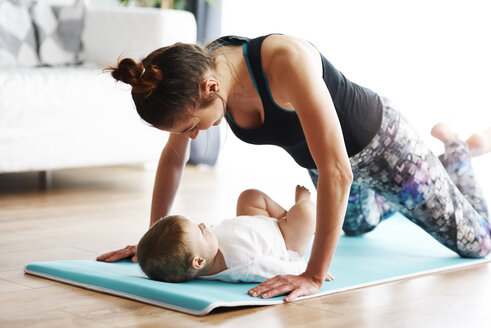 Mother with baby exercising on yoga mat at home - ABIF00333