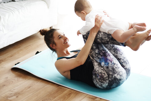 Mother and baby exercising on yoga mat at home - ABIF00336