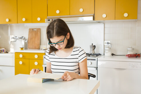 Girl reading a book in kitchen - LVF06865