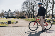 Senior man with bike in a park - GUSF00633