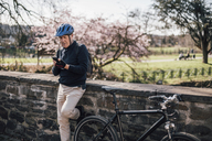 Senior man with cycling helmet using smartphone - GUSF00636