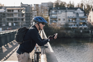 Senior man with cyclist helmet using smartphone on bridge - GUSF00639