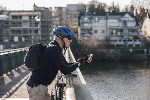 Senior man with cyclist helmet using smartphone on bridge - GUSF00639