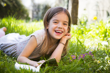 Smiling girl lying on meadow, reading a book - LVF06869