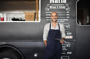 Portrait of smiling male owner holding tablet computer while standing against food truck - CAVF39474