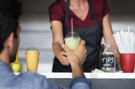 Midsection of female owner giving smoothie to customer at food truck - CAVF39486