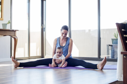 Mother holding baby boy while exercising at home - CAVF39528