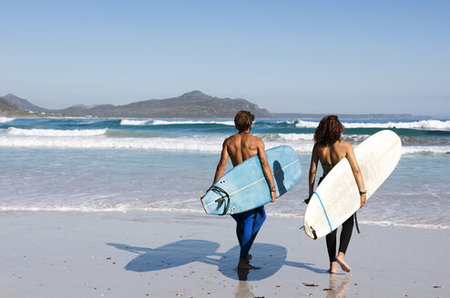 Rear view of friends carrying surfboards at beach during sunny day - CAVF39561