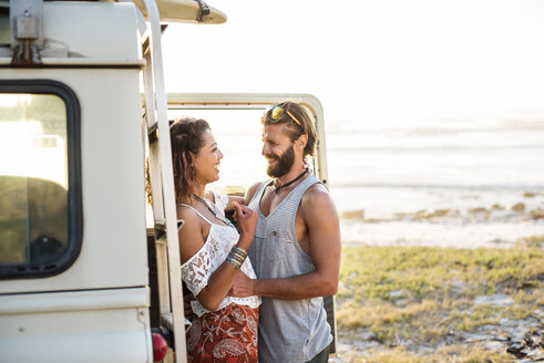 Cheerful couple standing by off-road vehicle at beach against clear sky - CAVF39594