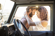 Couple romancing while standing by off-road vehicle seen through window - CAVF39600