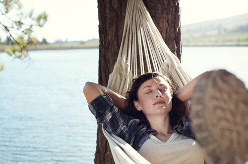 Woman sleeping on hammock at lakeshore - CAVF39624