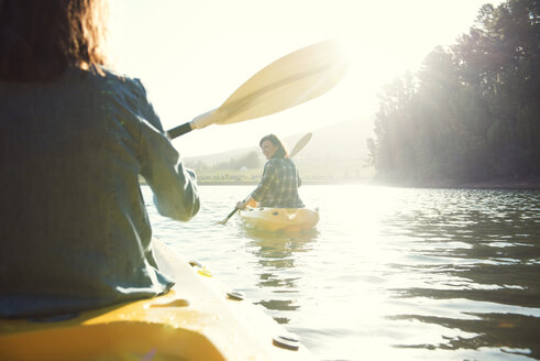 Rear view of female friends kayaking on lake against sky during sunny day - CAVF39630