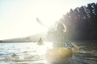 Rear view of female friends kayaking on lake during sunny day - CAVF39633