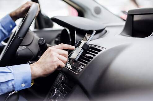 Cropped image of businessman using GPS on smart phone in car - CAVF39729