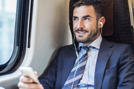 Smiling businessman listening music through smart phone in train - CAVF39750