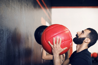 Side view of man throwing medicine ball at gym - CAVF39759