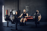 Determined athletes exercising on rowing machine at gym - CAVF39765