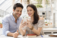 Happy couple using smart phone at sidewalk cafe - CAVF39786