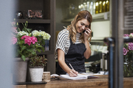 Florist writing in note pad while using mobile phone - CAVF39849