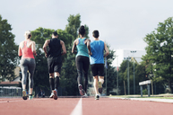 Rear view of athletes running on track - CAVF39870