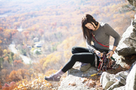 Woman looking at climbing equipment while sitting on rock - CAVF39915