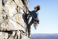 Man rock climbing against clear sky - CAVF39921