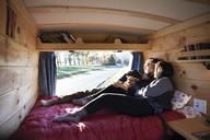 Couple kissing while relaxing in camper van - CAVF39924