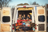 Couple looking at friend reading book while relaxing on bed in camper van - CAVF39936