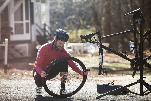Athlete adjusting bicycle tire on road during sunny day - CAVF39948